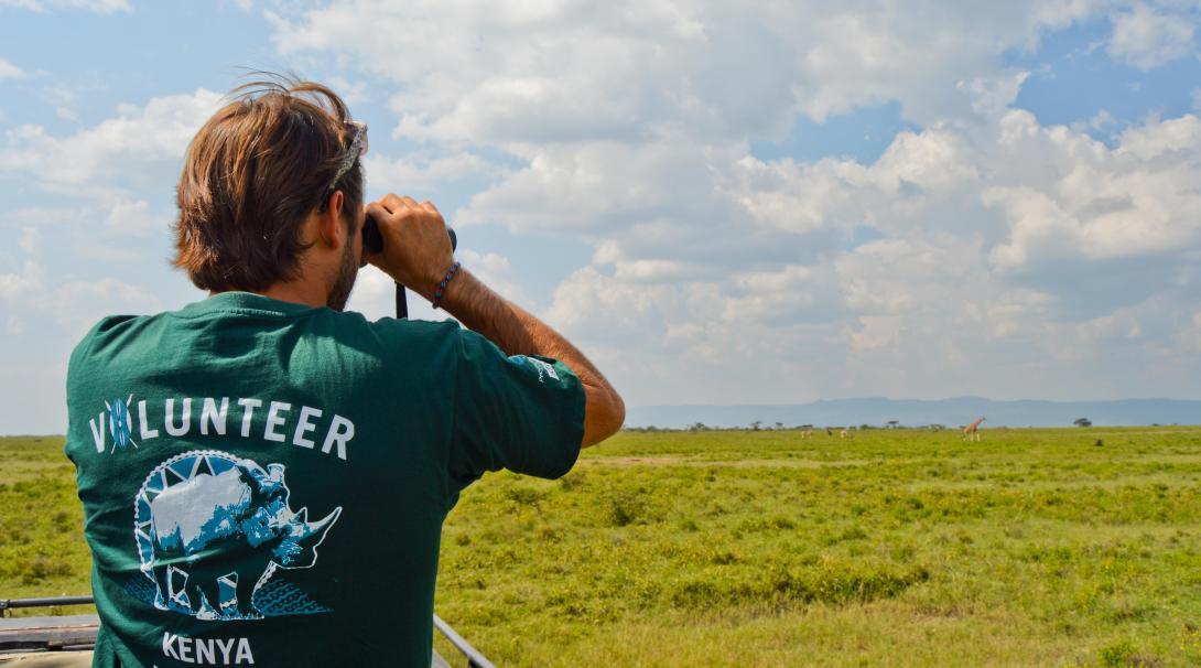 A conservation volunteer in Kenya searches for wildlife